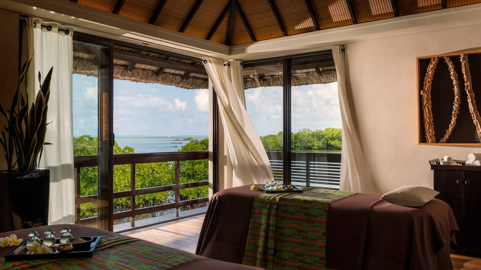 Two massage tables with colourful textiles by corner windows with white curtains, ocean view