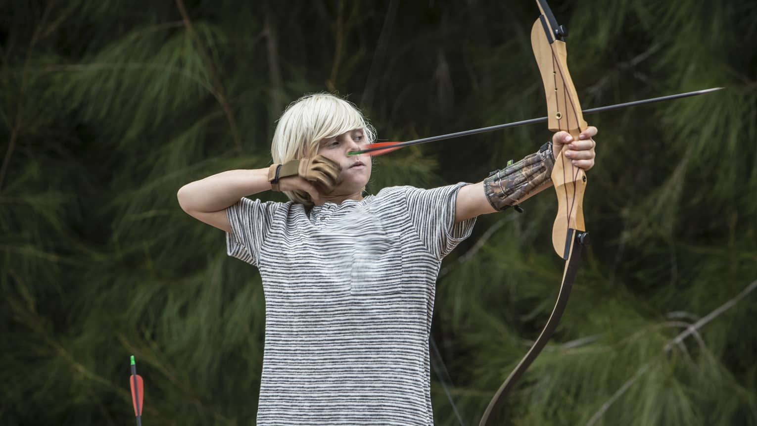 A young boy steadies his bow as he prepares to shoot an arrow at a target