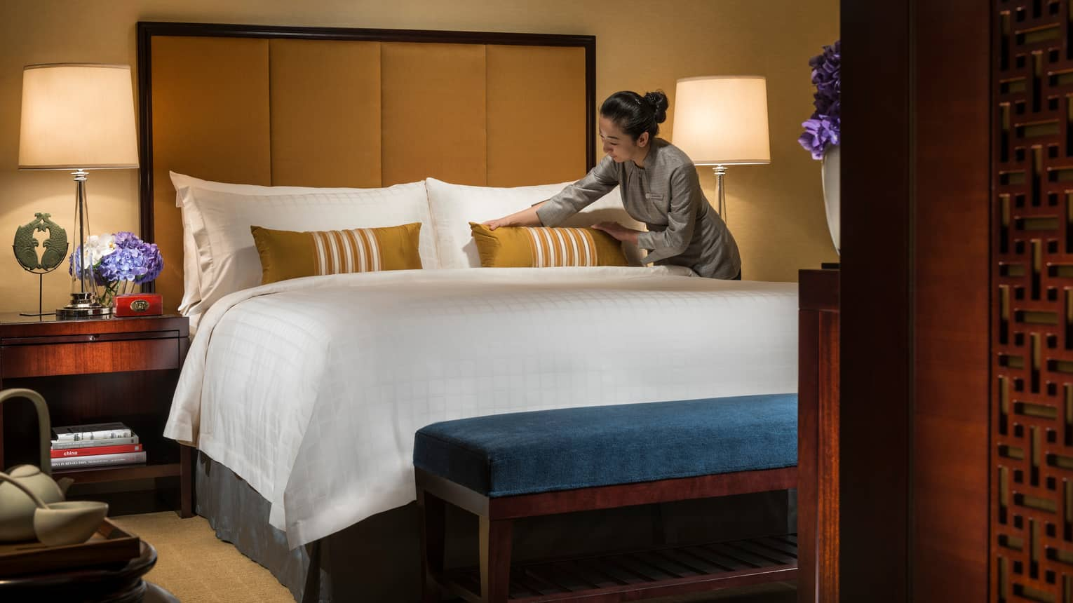 Hotel staff makes bed, adjusts gold accent pillow on white pillows, linens