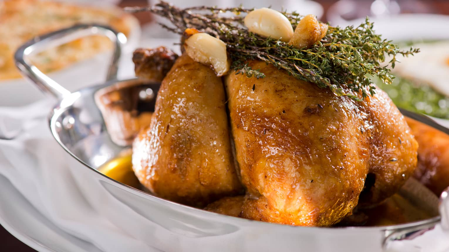 Rotisserie Baby Chicken in silver dish topped with roasted garlic cloves, crispy herbs