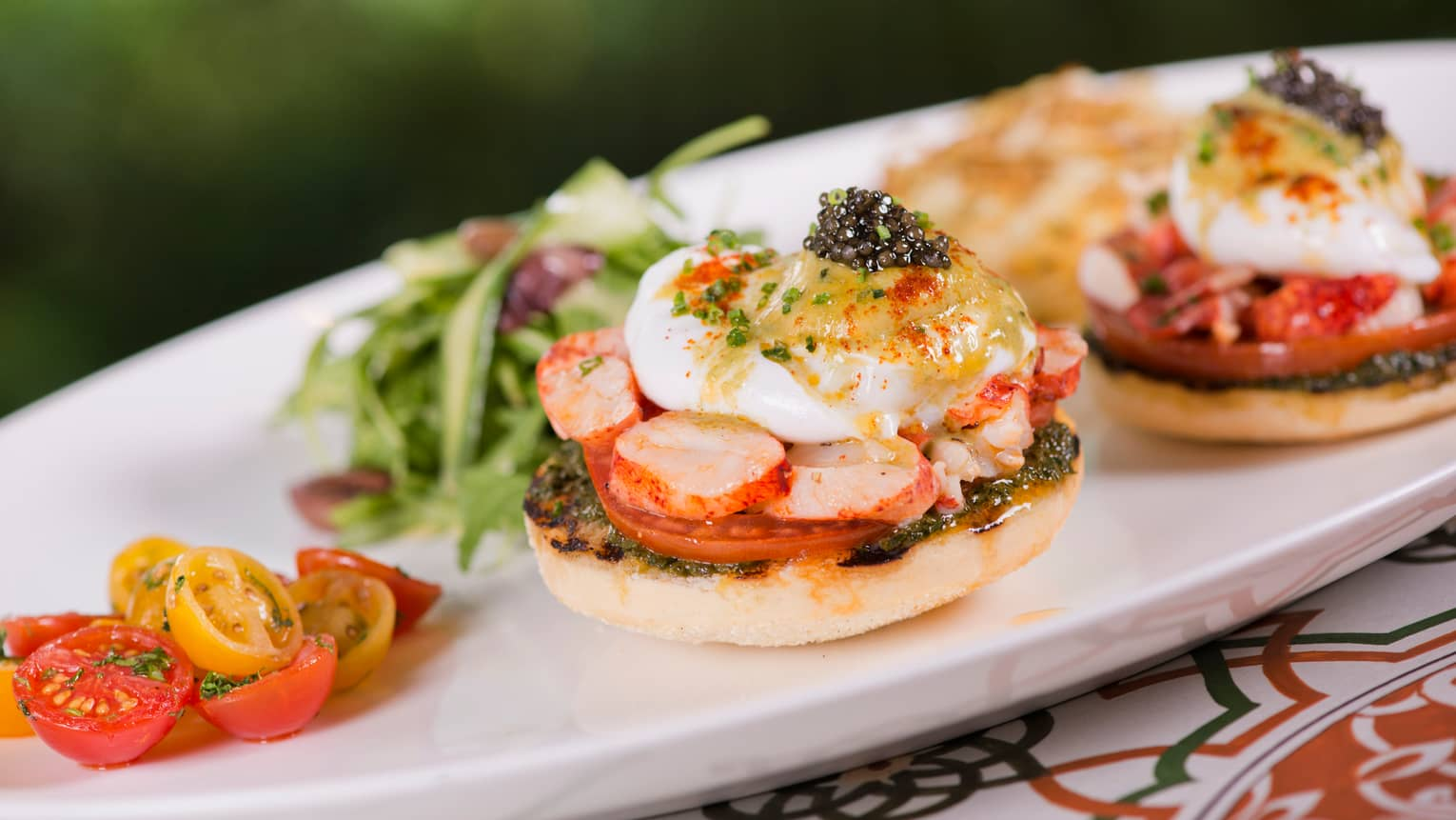 Forest Benedict toasted English muffins with poached eggs, turkey ham, tomatoes on white tray