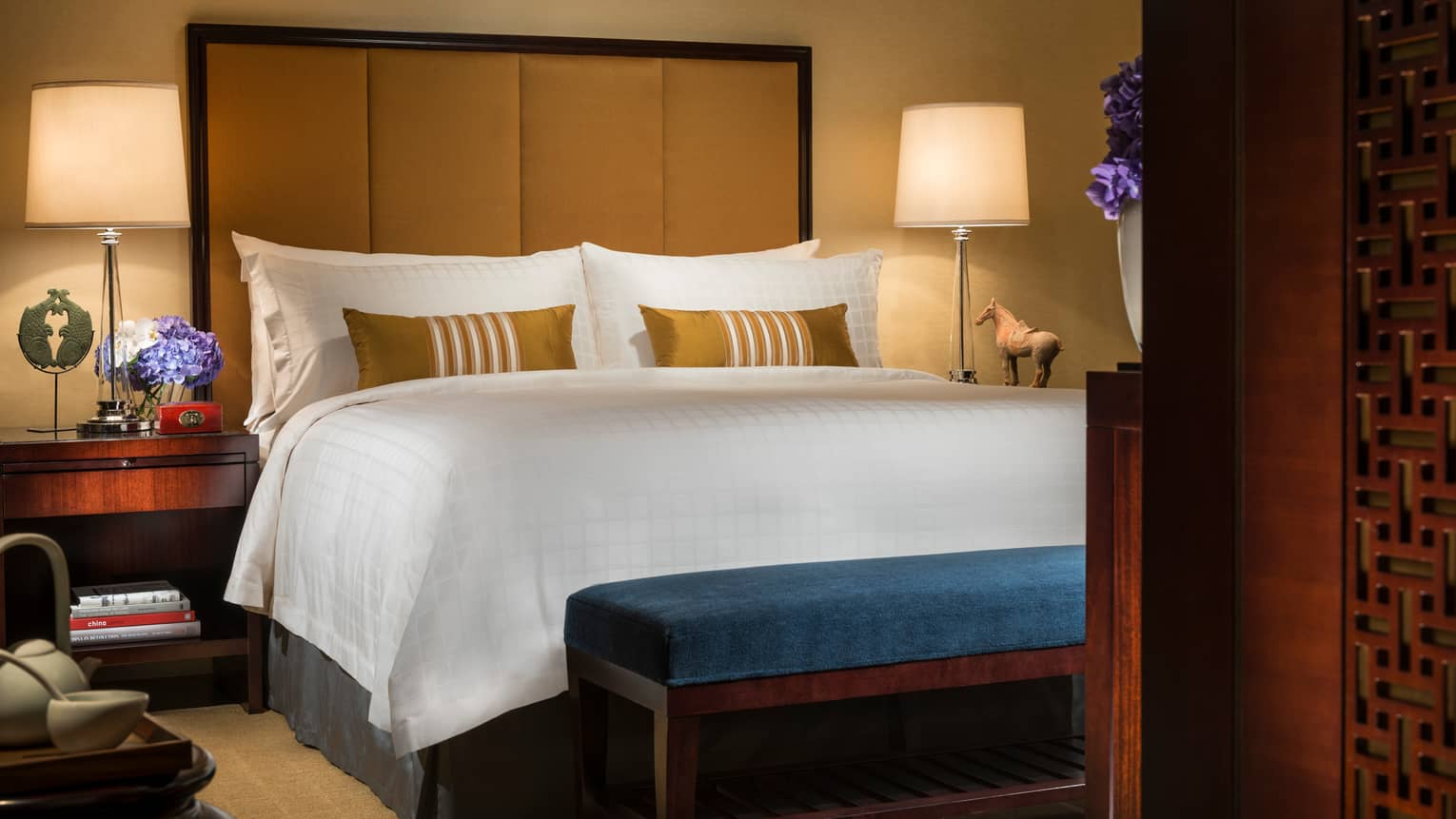 Deluxe Room bed with tall padded headboard, small blue bench at foot, sculptures and art on nightstand