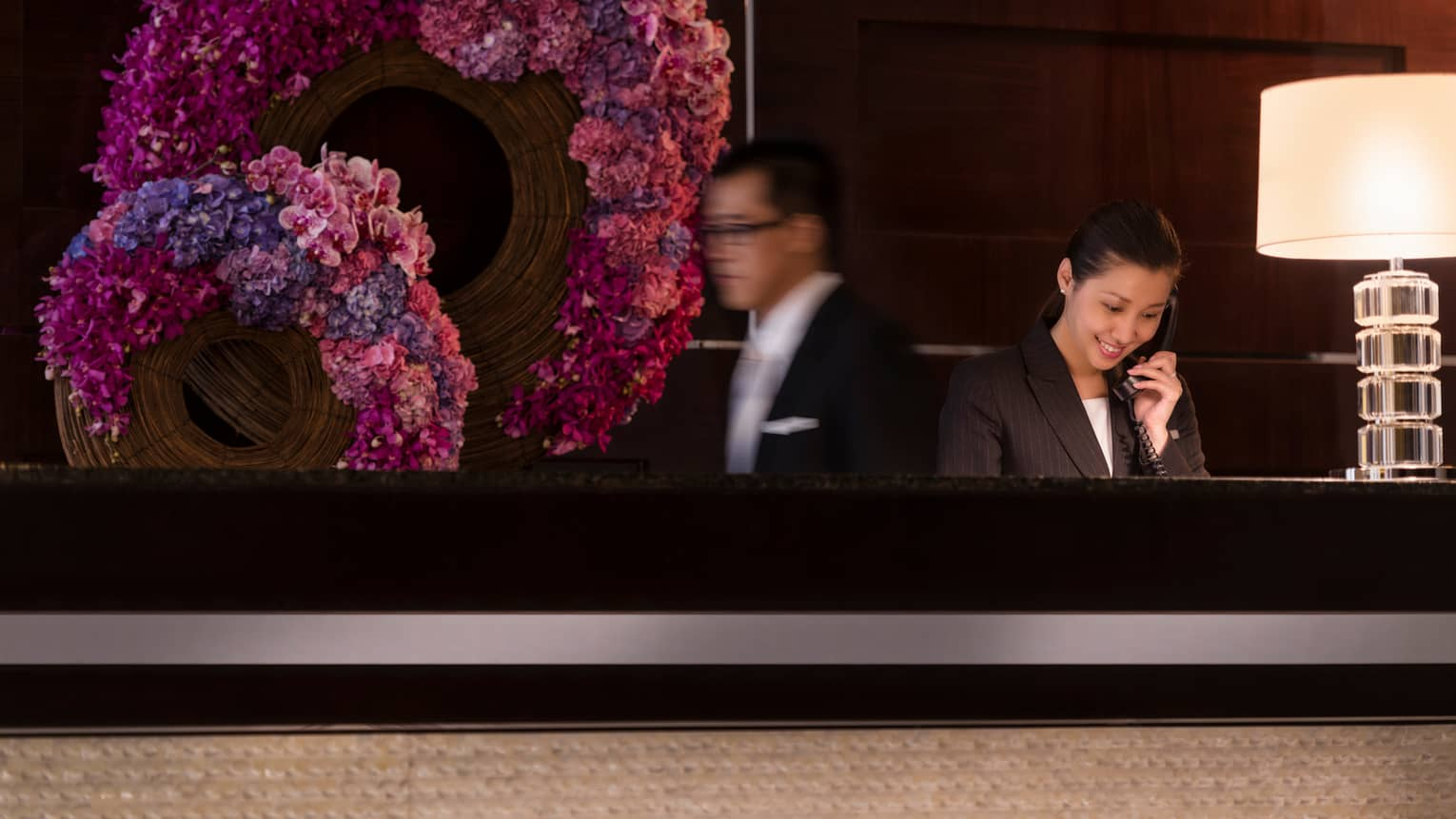 Staff at concierge desk in front of pink-and-purple floral wreaths