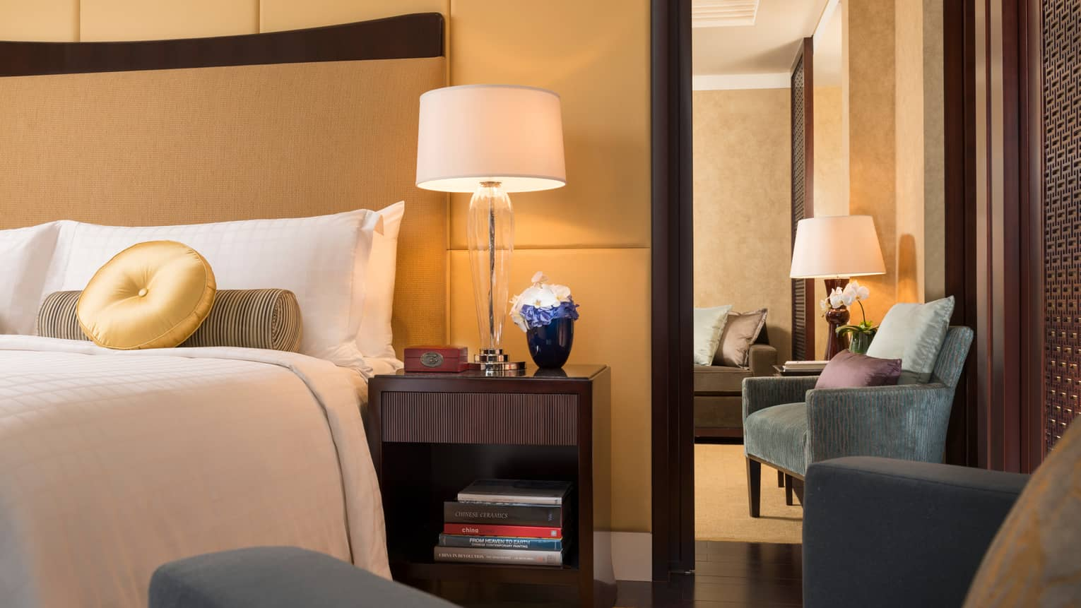 Ambassador Suite corner of bed with round gold pillow, armchair, nightstand with lamp, flowers