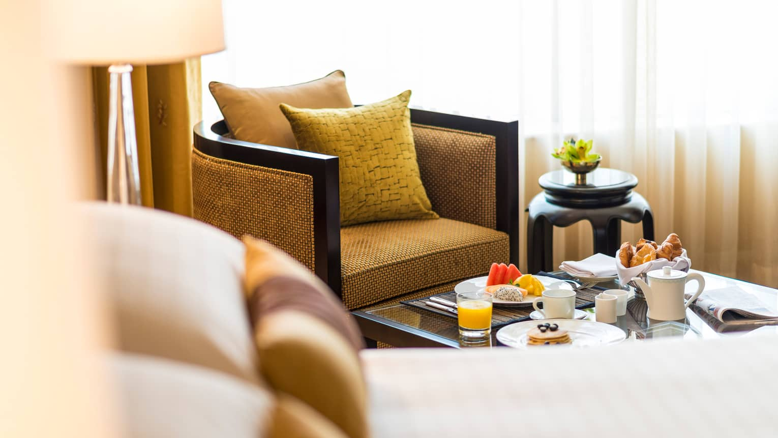 Gold armchair, pillow by in-room dining table with fresh fruit, pastries, coffee, juice