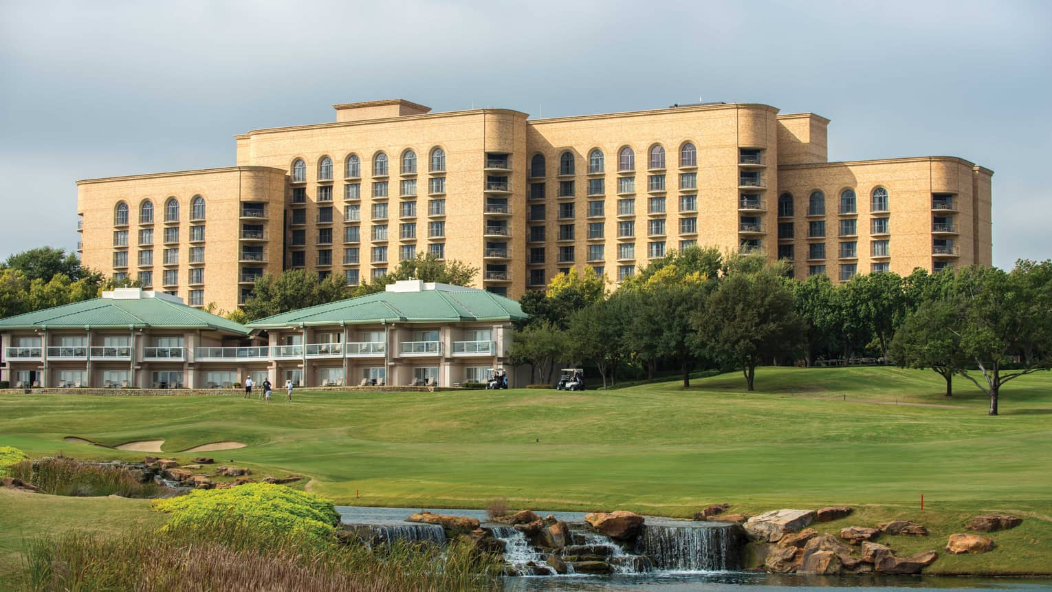 Exterior view of Four Seasons Hotel Dallas golf resort buildings at top of greens