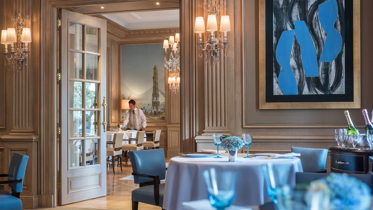 Il Lago dining room with high ceilings, cream walls and bright blue painting, chairs, glassware