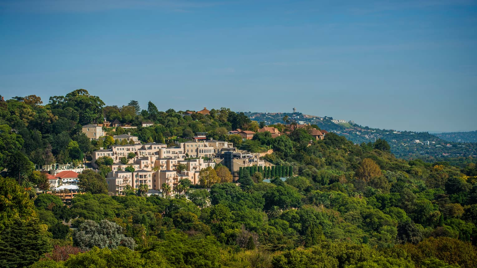 Aerial view of pink Four Seasons Hotel The Westcliff, Johannesburg building in green mountain