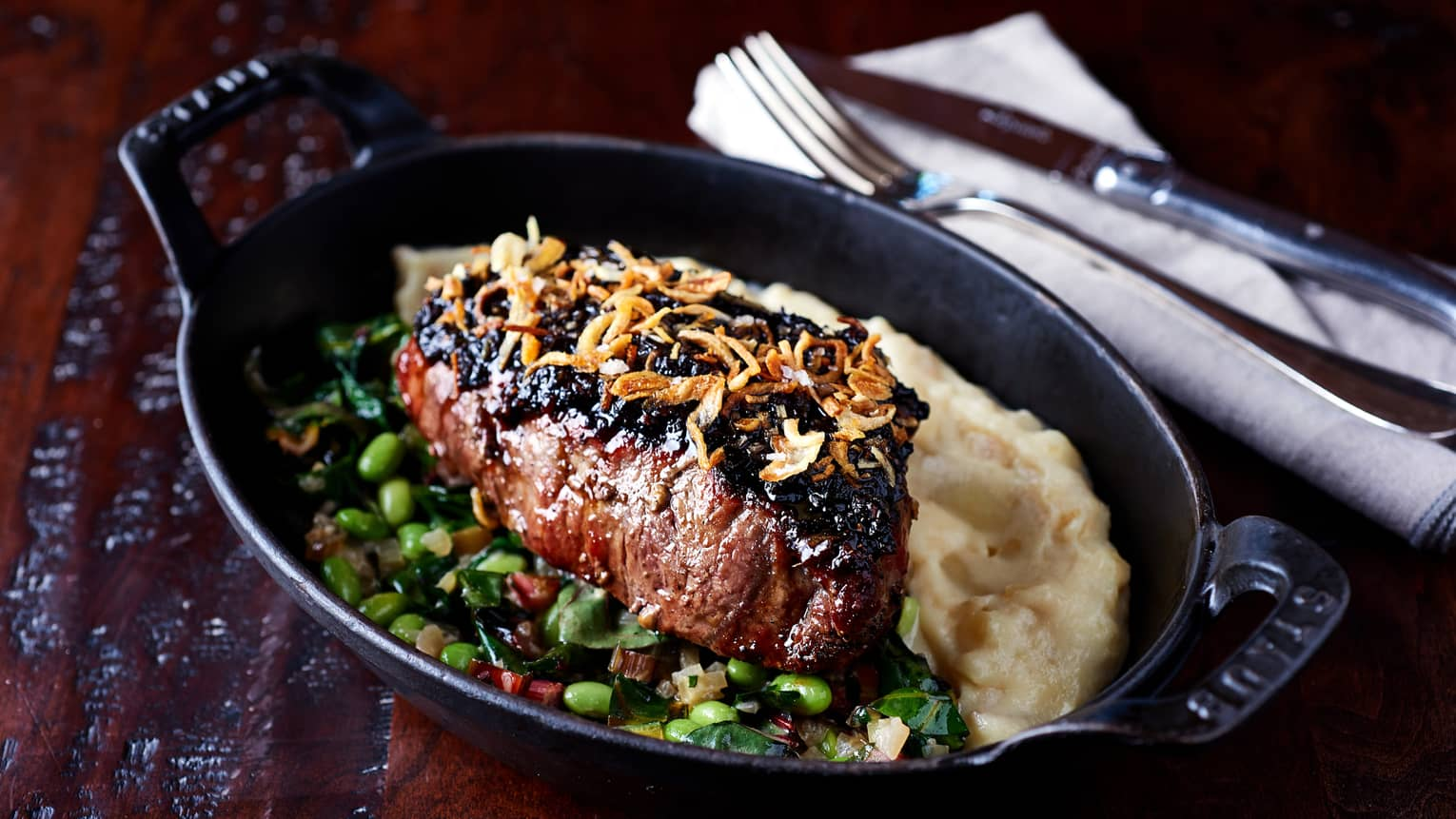 Charred wild boar steak topped with crispy onion in skillet with green soy beans, sauce