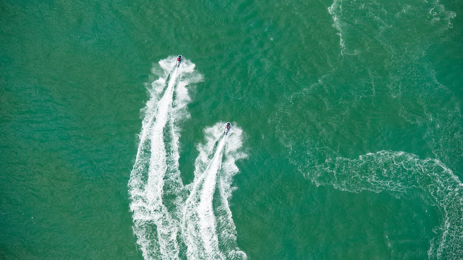 Aerial view of two jet skis, trails on water in ocean