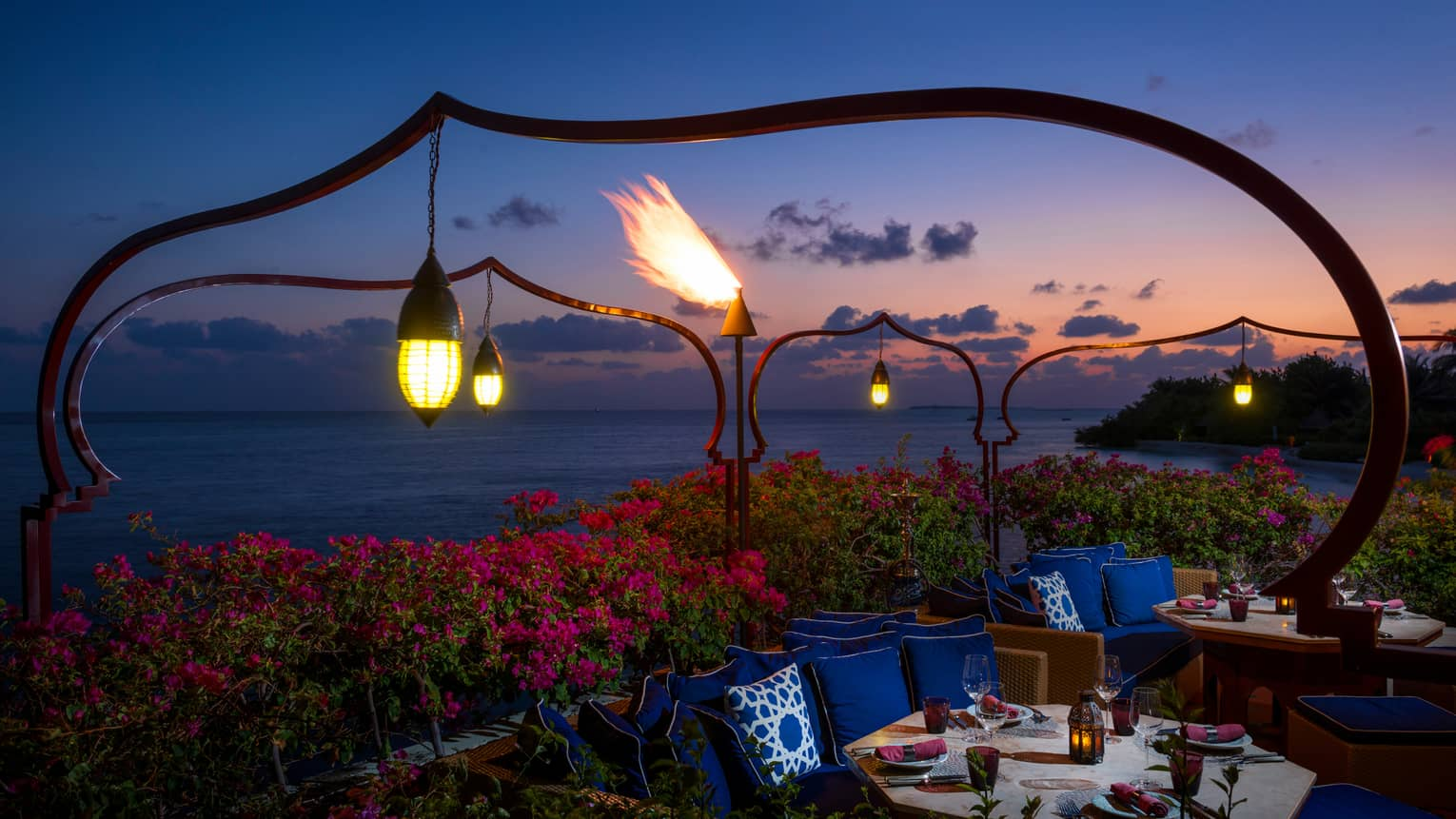 Lanterns hang over pink tropical gardens, booths with dining tables, plush blue pillows at night
