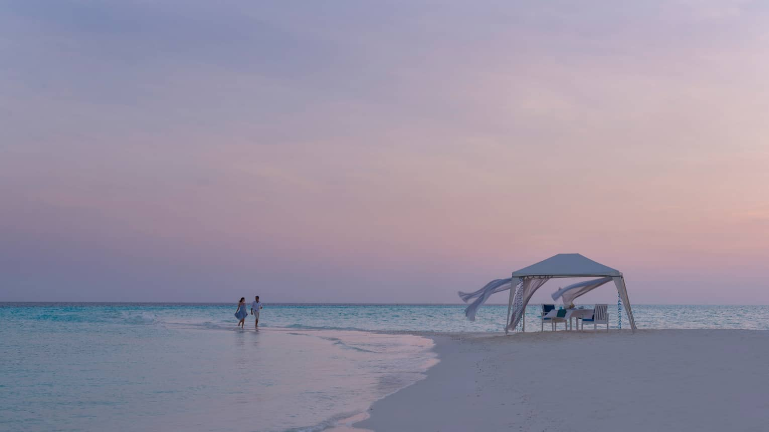 Couple walks across tide, sand beach to cabana with flowing white curtains, pink sunset