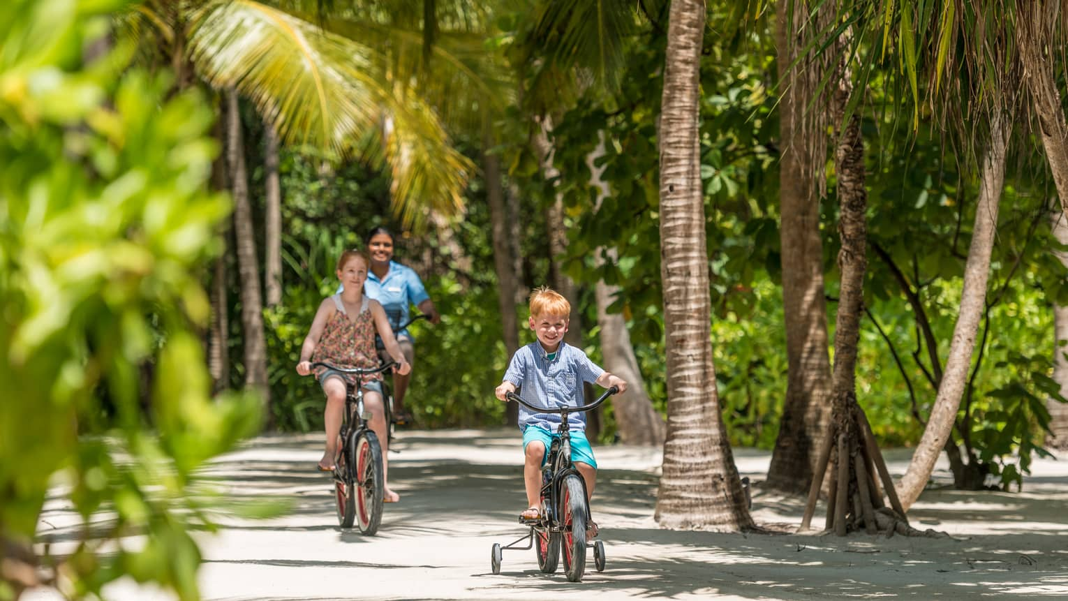 Young boy rides tricycle as older girl, hotel staff ride bicycles on forest path behind him
