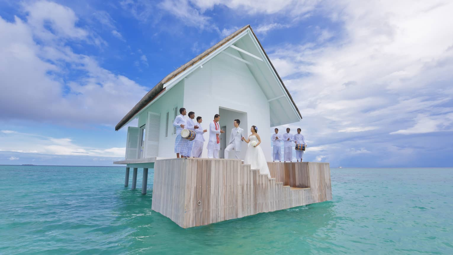 Wedding ceremony on steps of small white bungalow in middle of blue lagoon