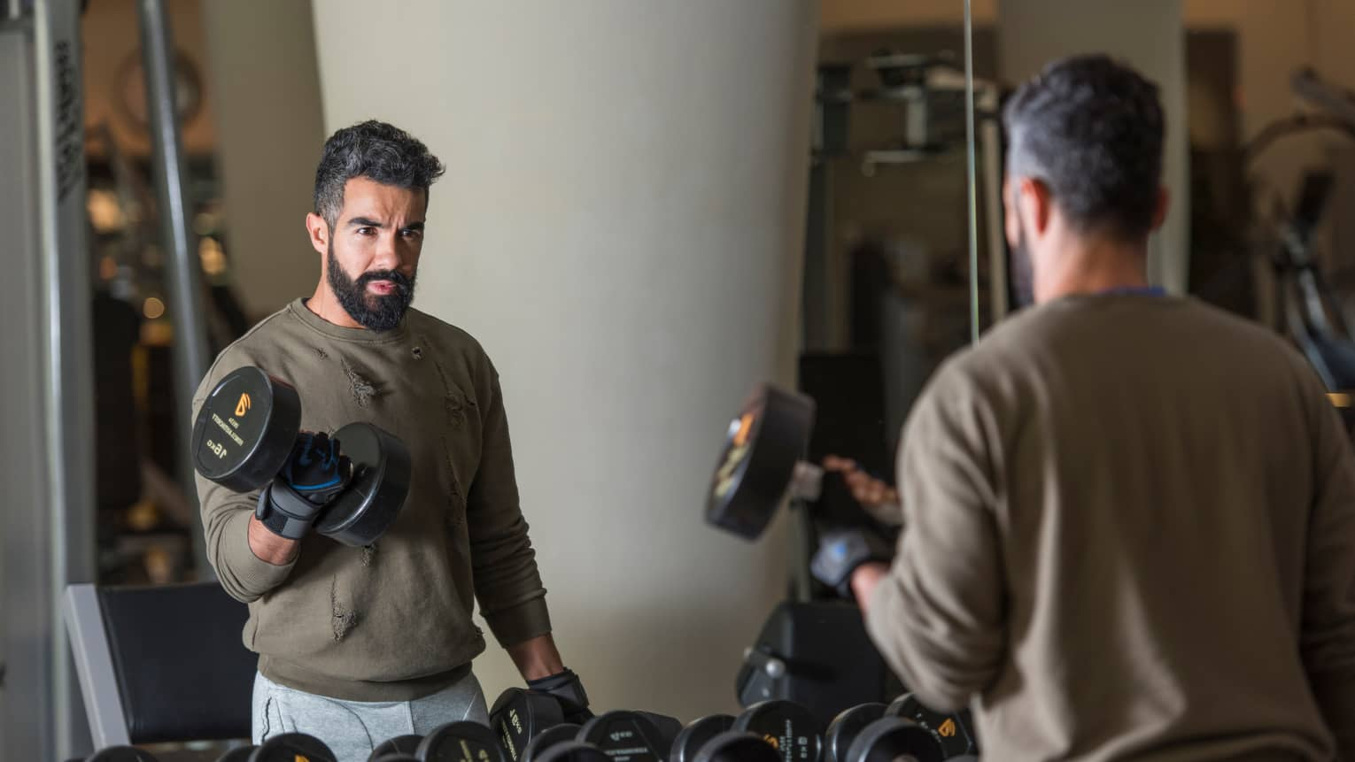 Man with beard wearing casual sweatshirt and sweatpants stands looks in gym mirror, lifts large hand weights