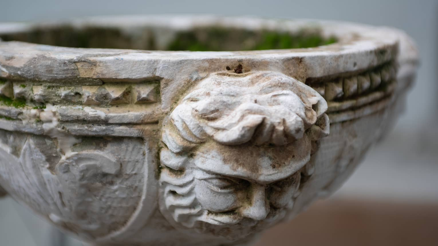 Historic detailing of a face engraved on stone planter