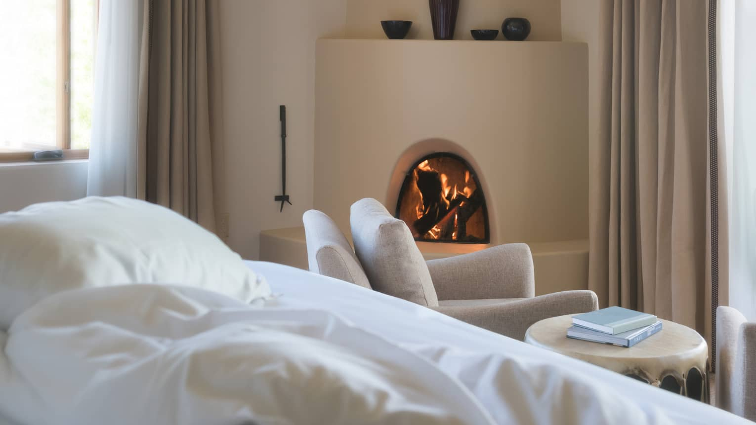 Hotel bed pillows, white armchair in front of curved clay fireplace, vases on mantle