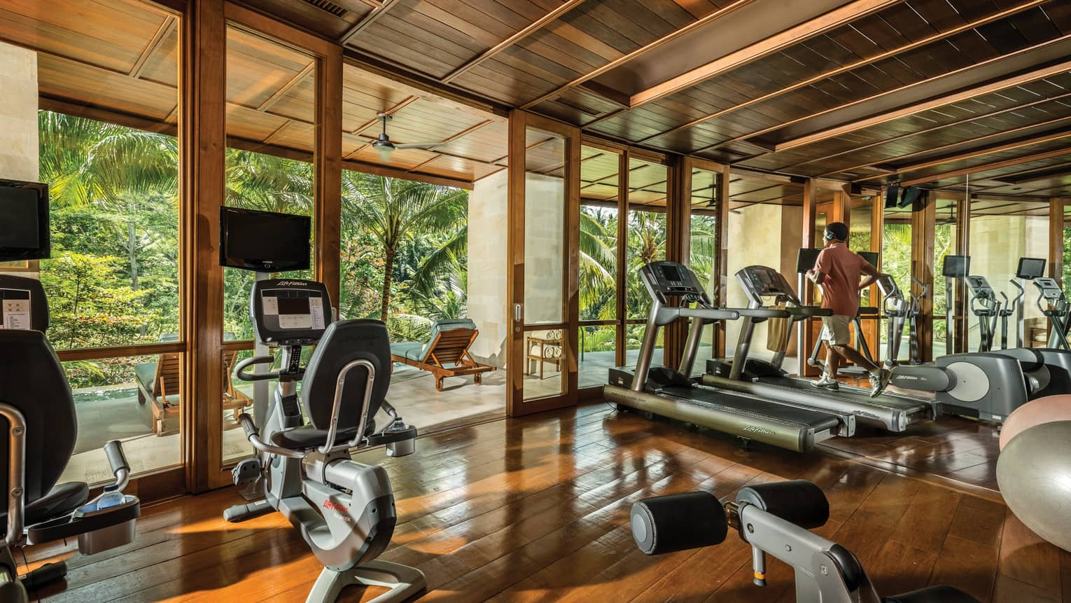 Sunny gym with fitness equipment, cardio machines, man running on treadmill near open door