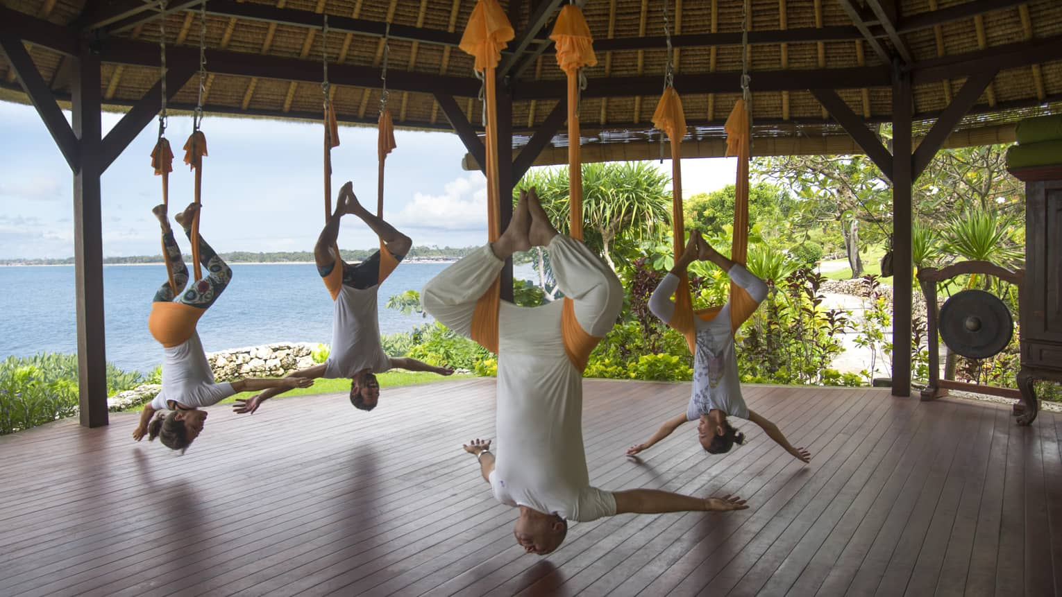 Guests participating in rope yoga, stretching as they are supported by the ceiling of an outdoor pavilion
