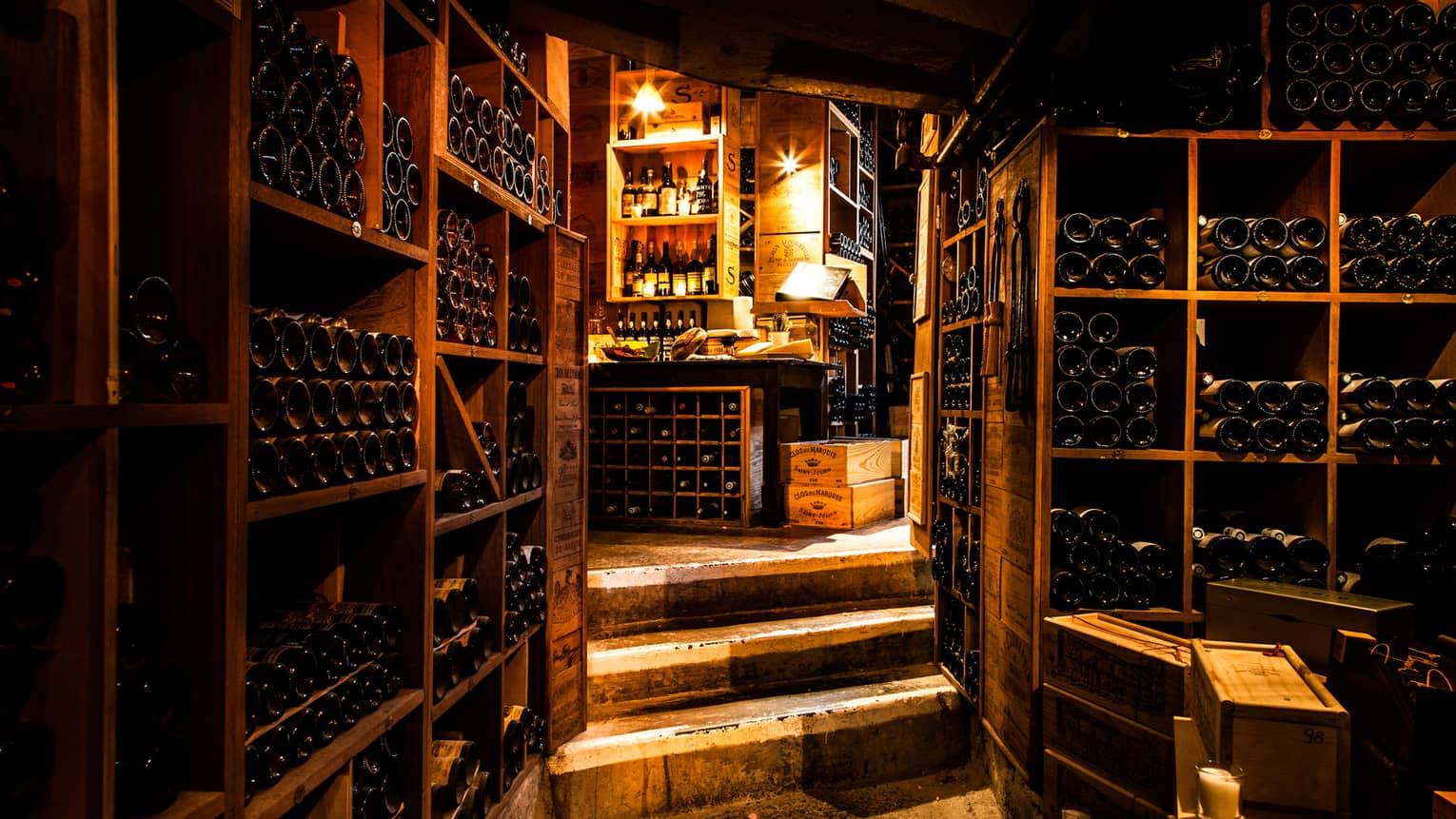 Vintage French wines line walls in dark wood cellar