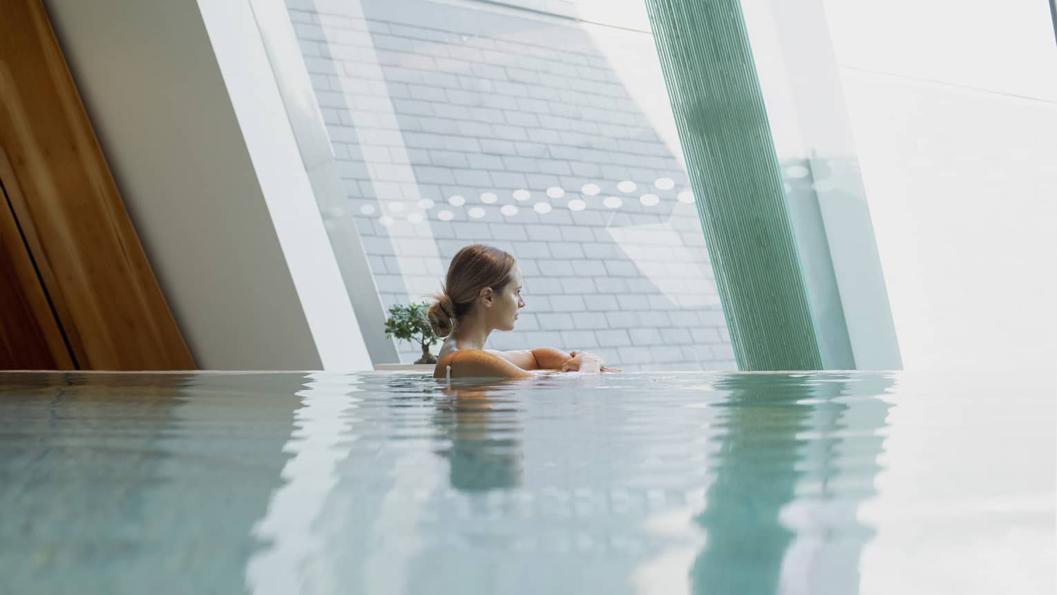 Woman in infinity-edge pool looking out window