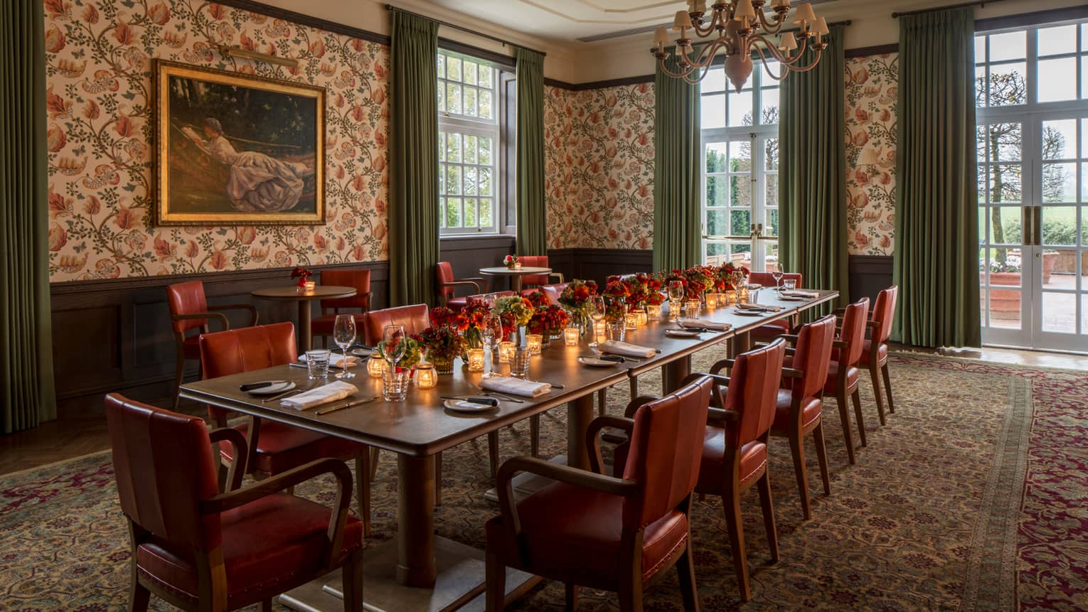 Long private dining table with candles, red flowers by corner windows, tall ceilings, floral wallpaper