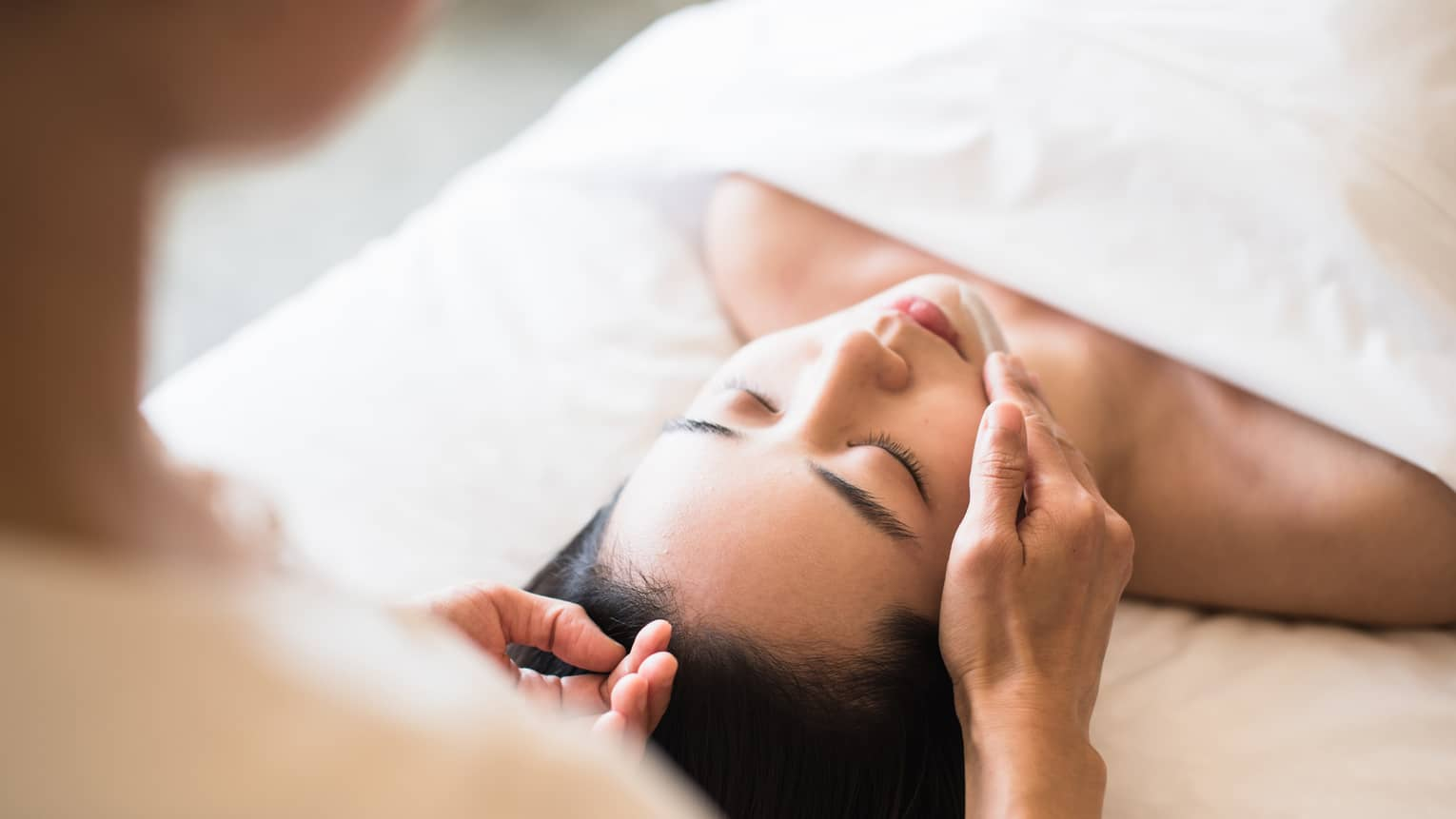 Woman lying under white sheet on massage table, eyes closed as spa staff rubs lotion on her chin