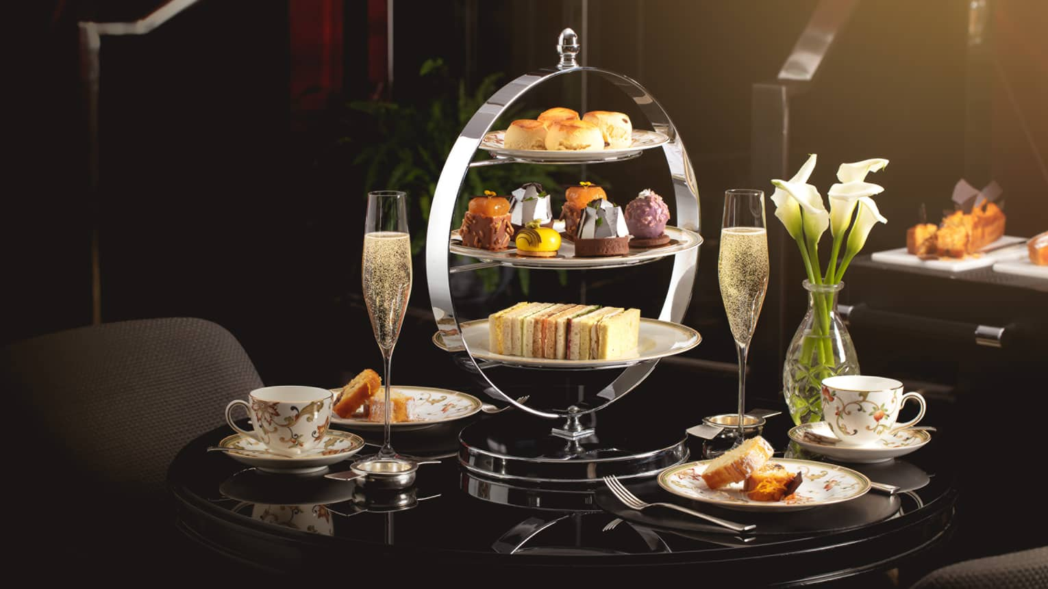Afternoon tea tray with sweets, tea cups and Champagne on table