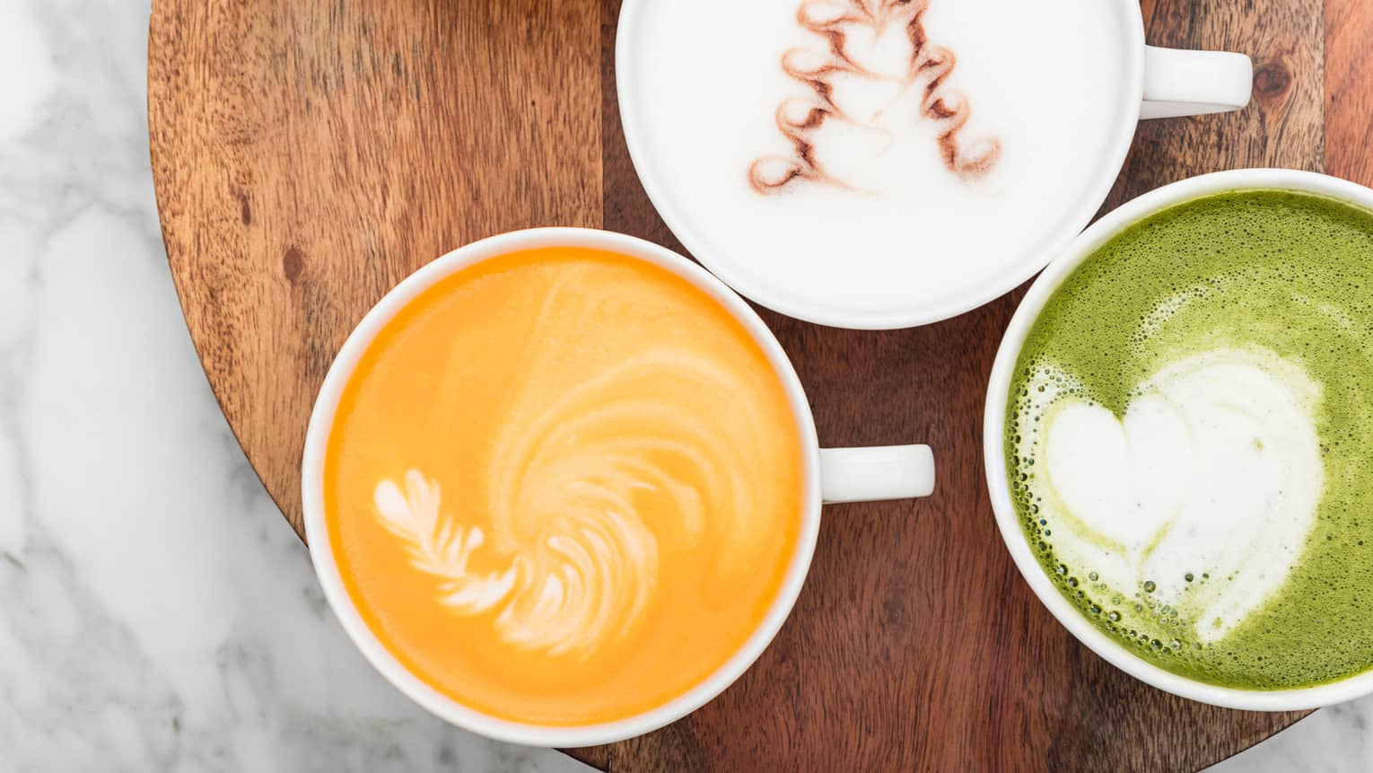 Aerial view of cups of three creamy milk, turmeric and matcha lattes