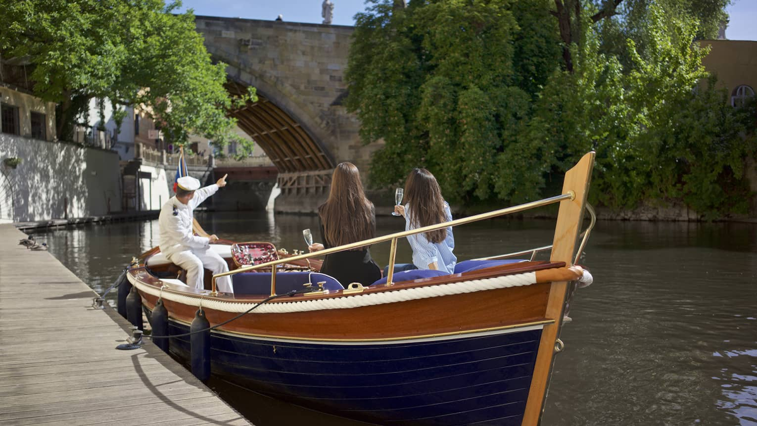 Small boat parked at dock on river, captain in white uniform points to bridge as two women drink Champagne