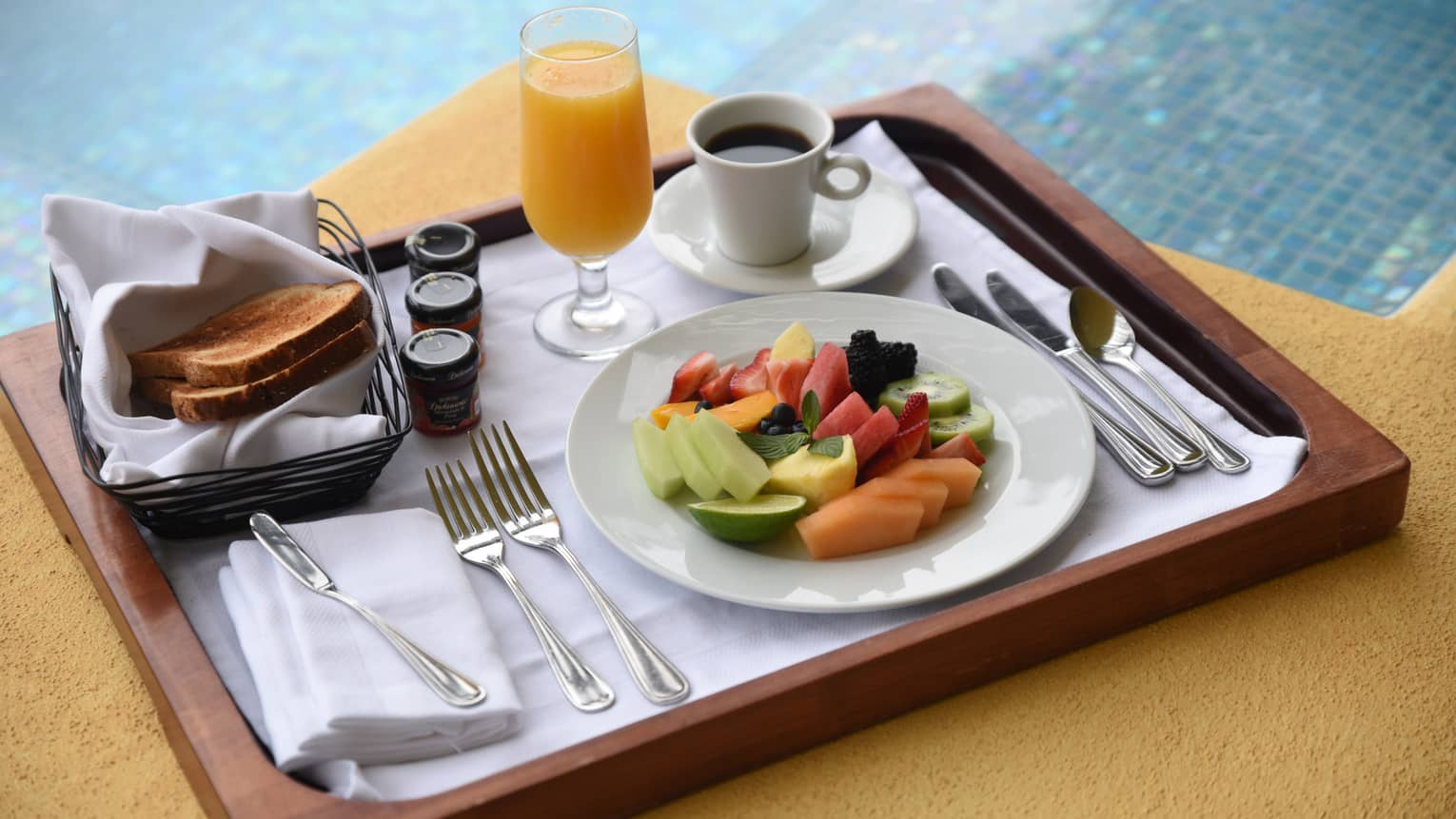 Fresh fruit slices on plate, coffee, orange juice, toast on wood tray by pool