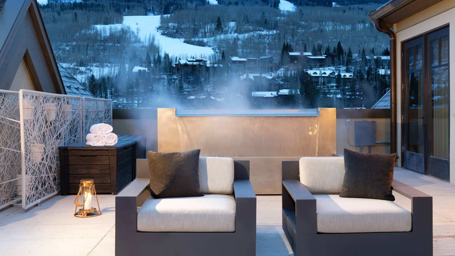 Plush patio armchairs in front of steaming fountain, snowy mountains in background