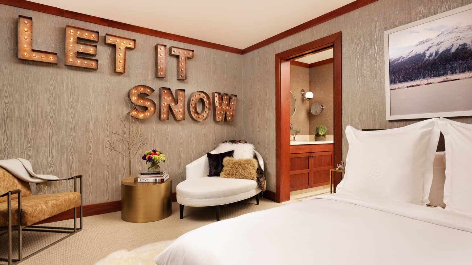Bed across from two armchairs, brass table, large sign with lights reading Let It Snow on wall