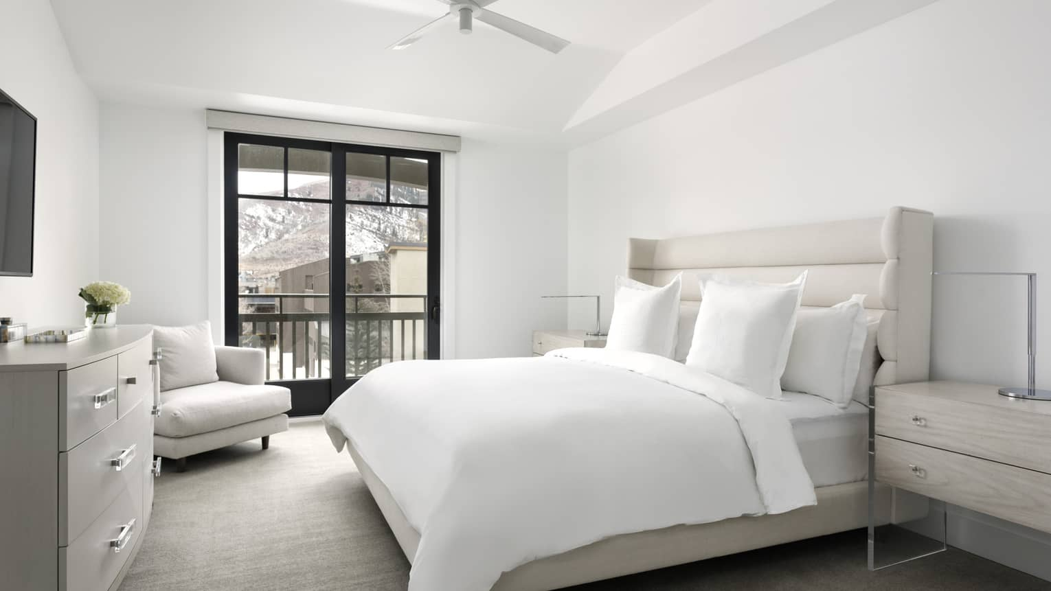 Bedroom with white walls, white king bed, light grey arm chair, dresser, walk-out balcony
