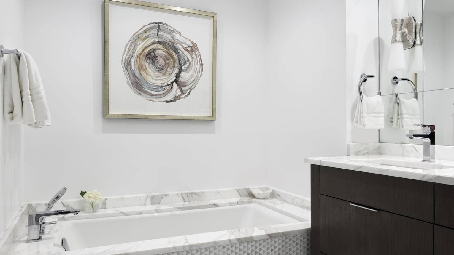 Bathroom with marble tub, artwork on wall, marble vanity