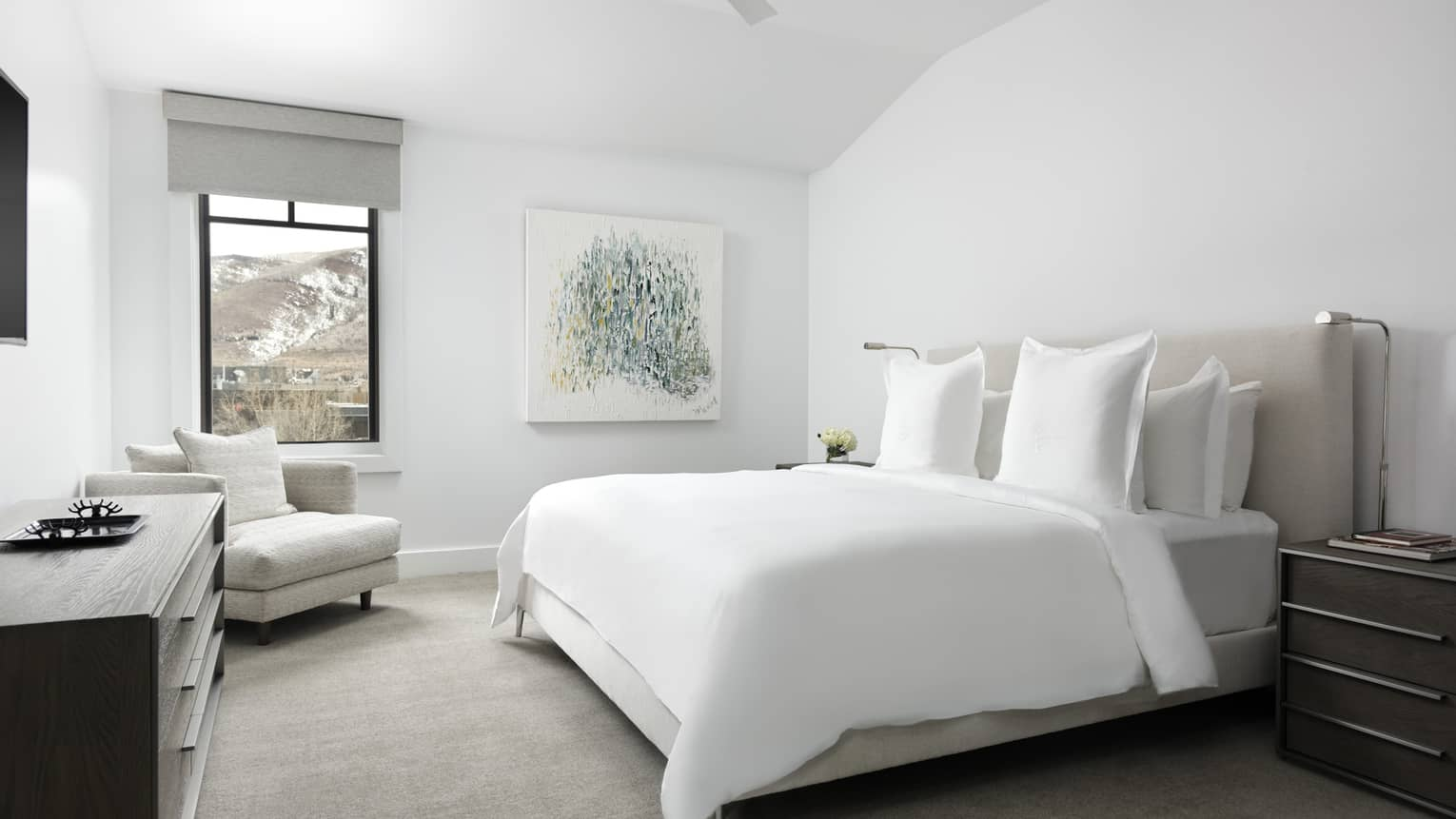 Bedroom with white walls, white king bed, light grey arm chair, dresser, window