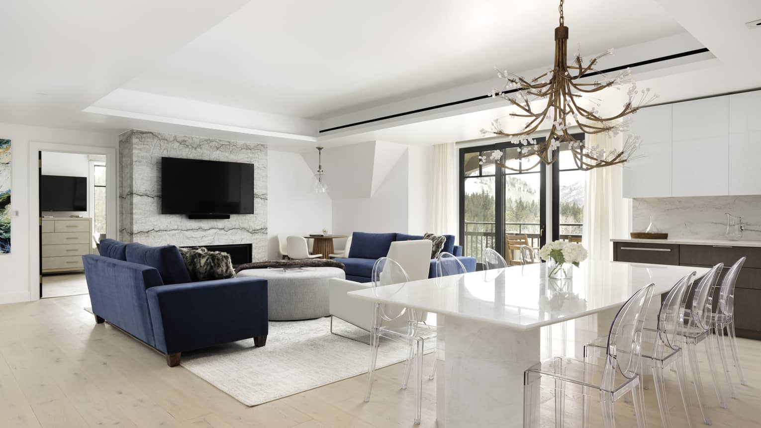 Living area with two dark blue sofas, fireplace, TV, opening to dining area with white table and 8 clear chairs