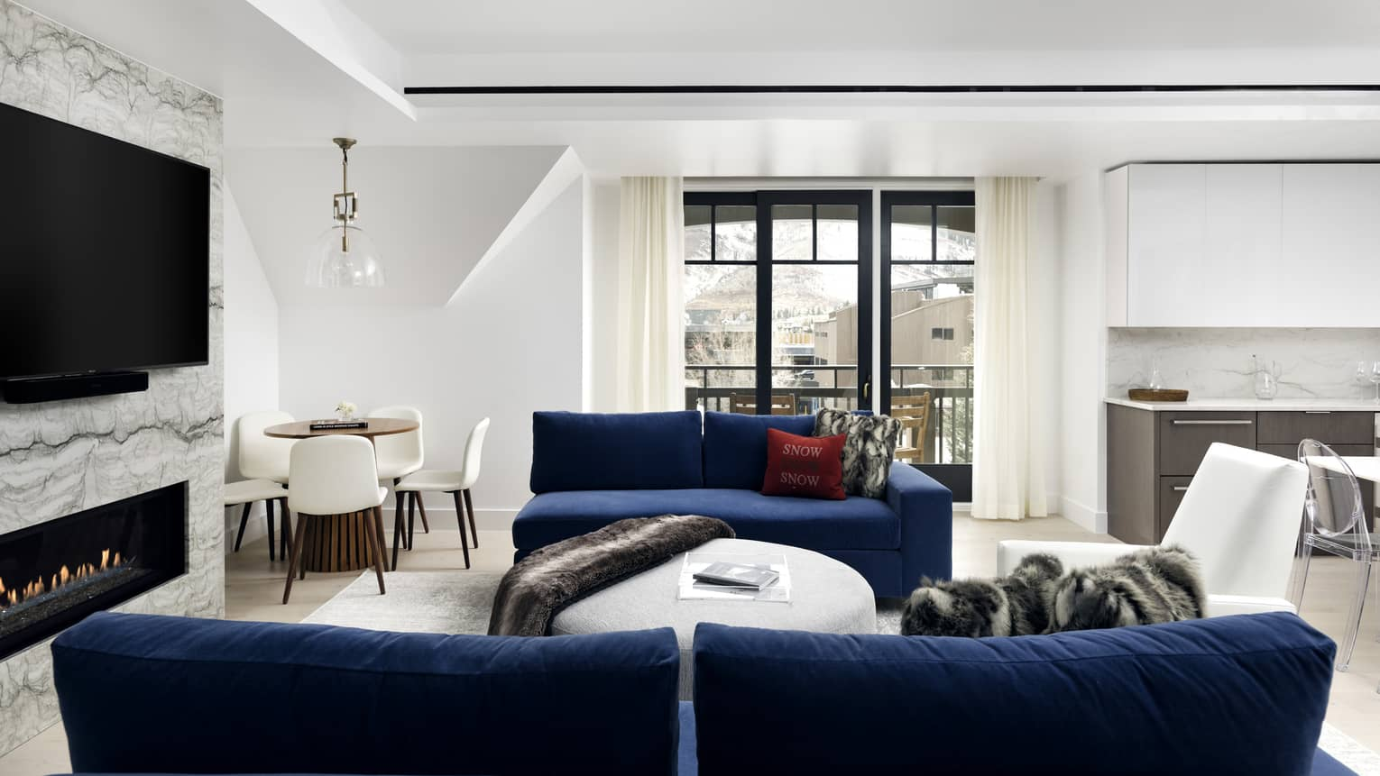 Living room with two dark blue sofas, fireplace, flat-screen TV, windows, white walls