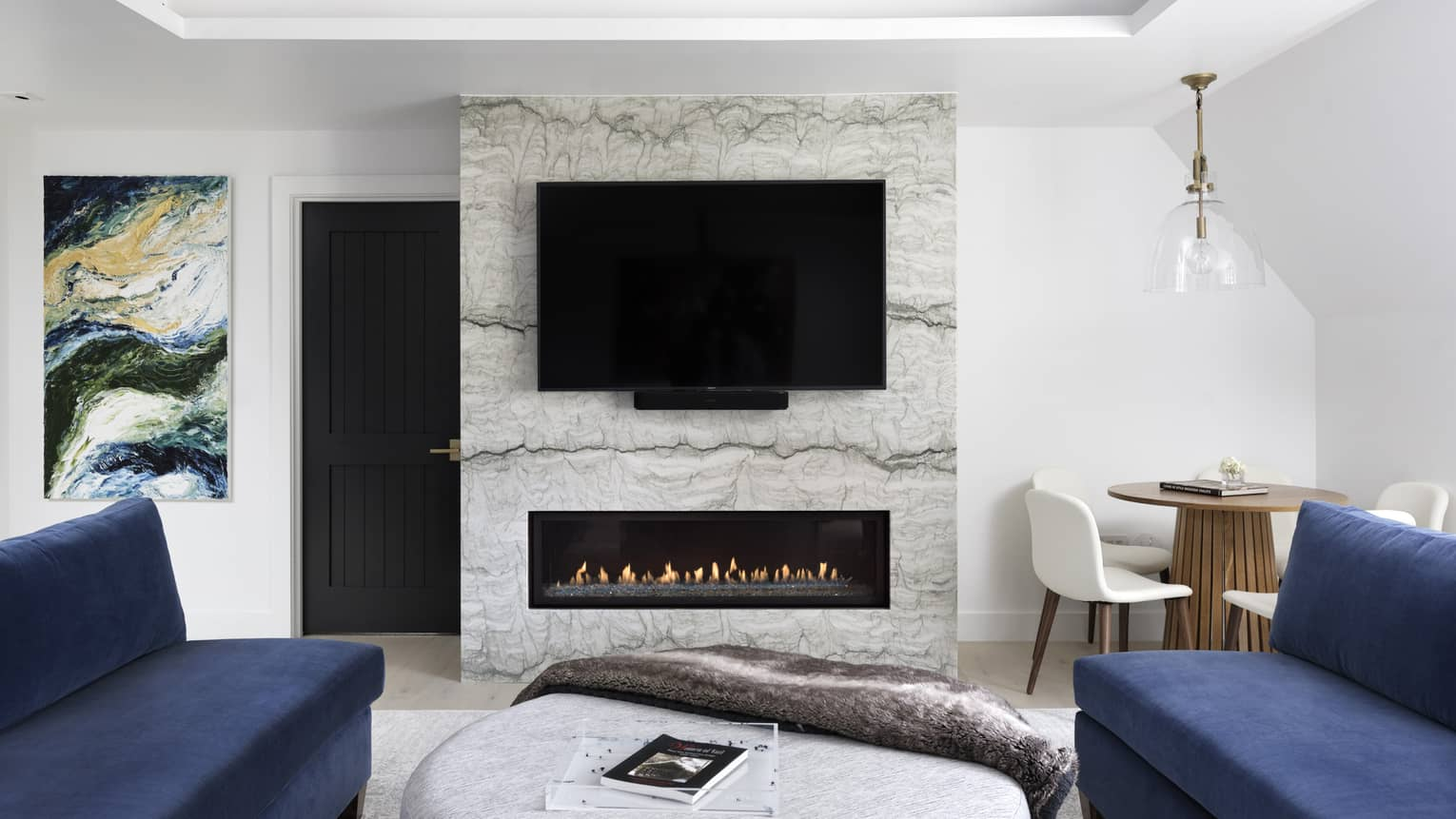 Modern fireplace with marble hearth, flat-screen TV, two dark blue sofas