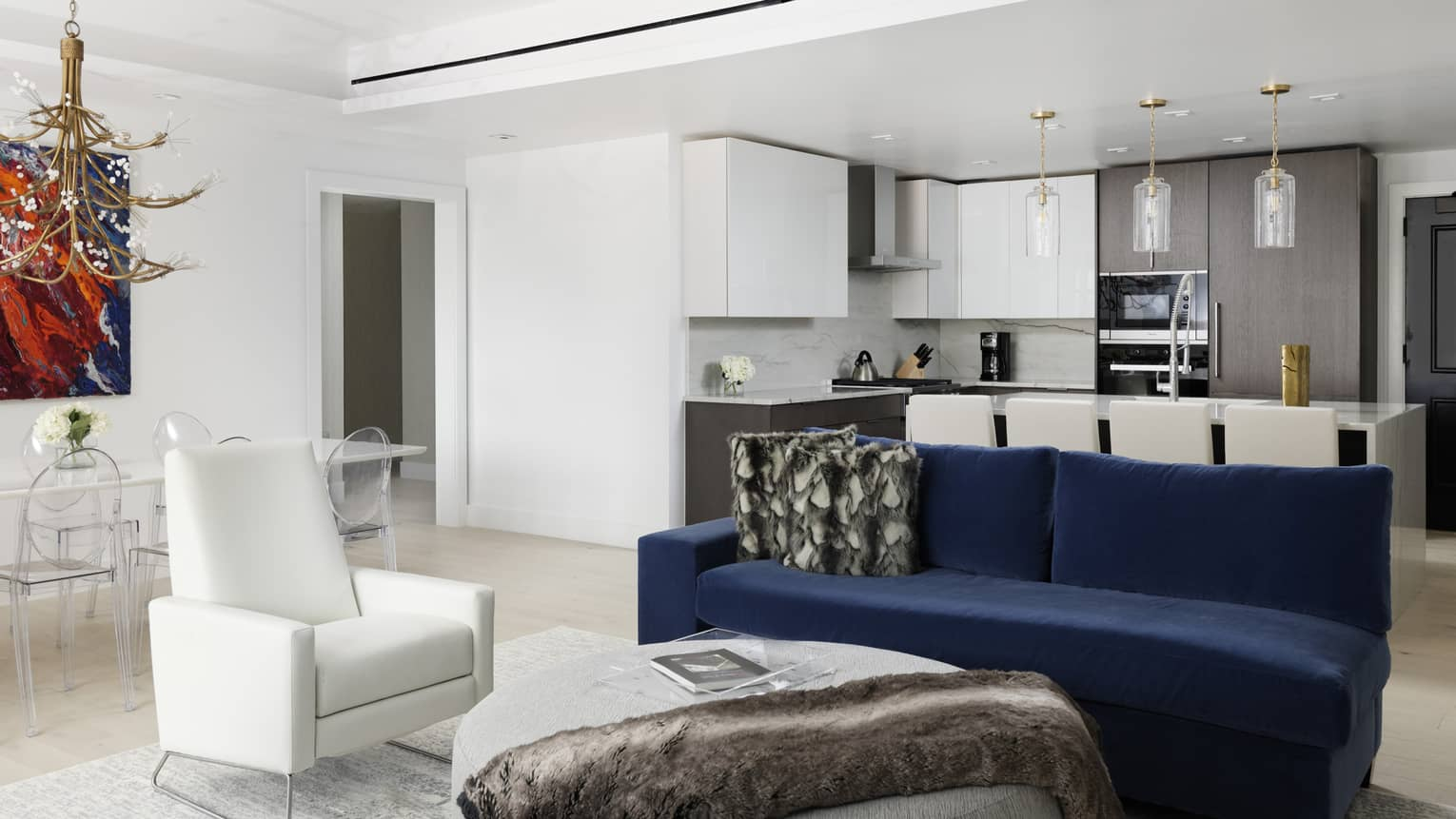 Living room with white walls and ceiling, dark blue sofa, white chair, kitchen in background
