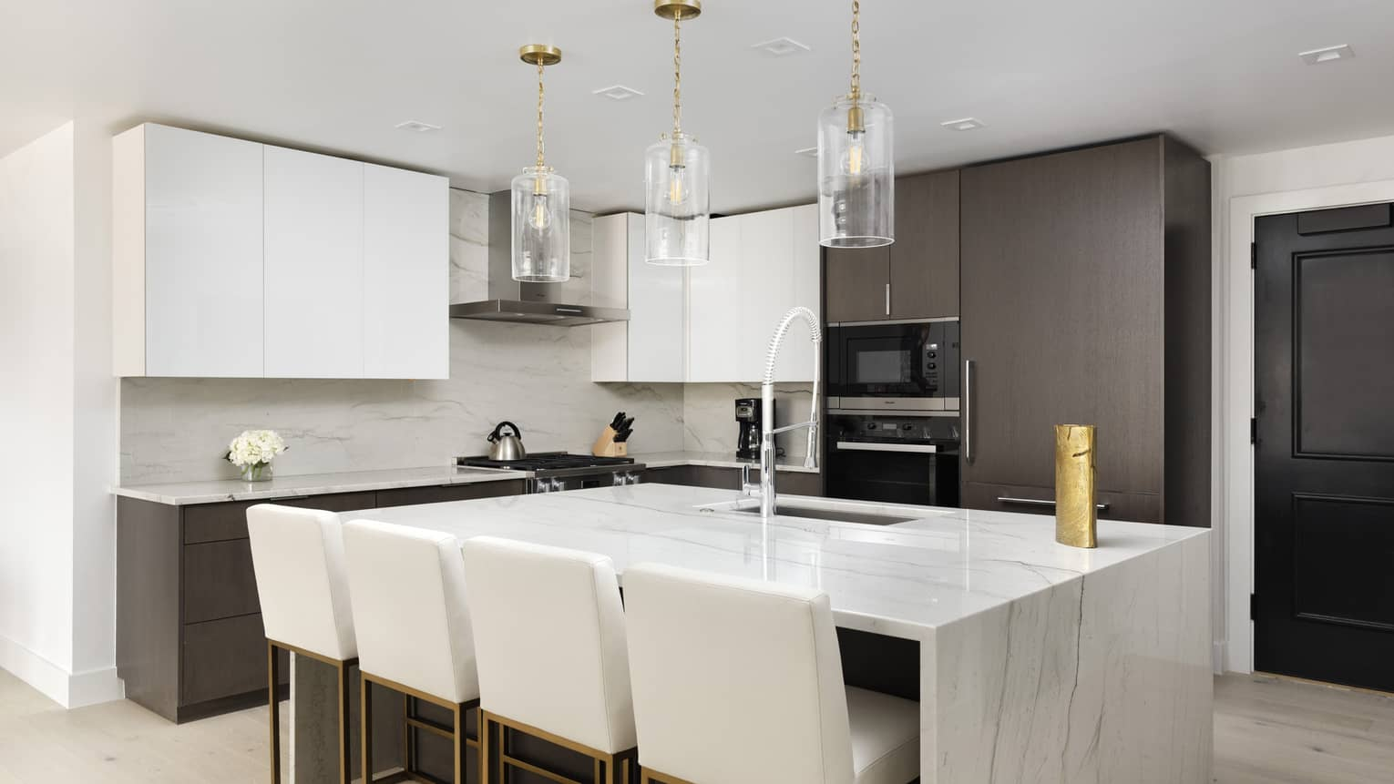 Kitchen with white marble island, four white counter-height chairs, three glass pendant lights