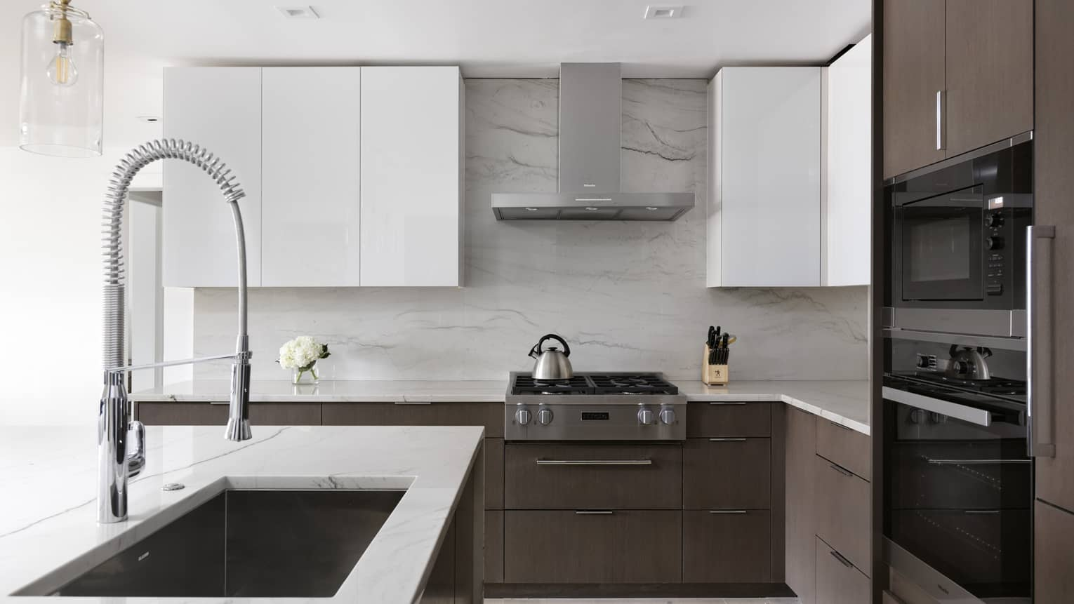 Kitchen with white cupboards and white marble countertops, dark wood lower cabinets