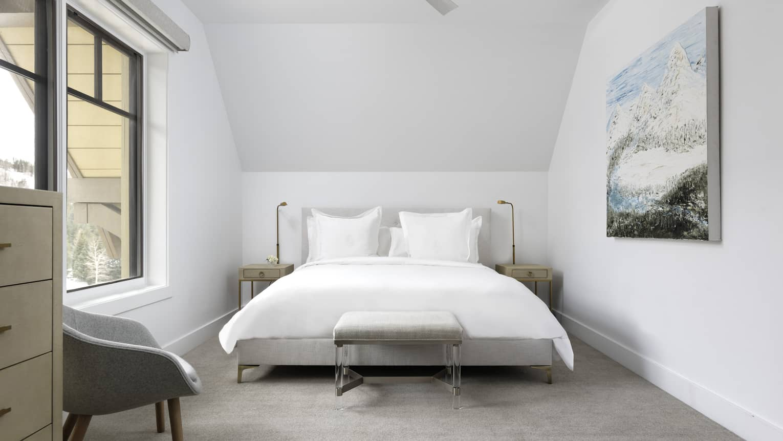 Bedroom with white walls, white king bed, light grey chair, artwork, window
