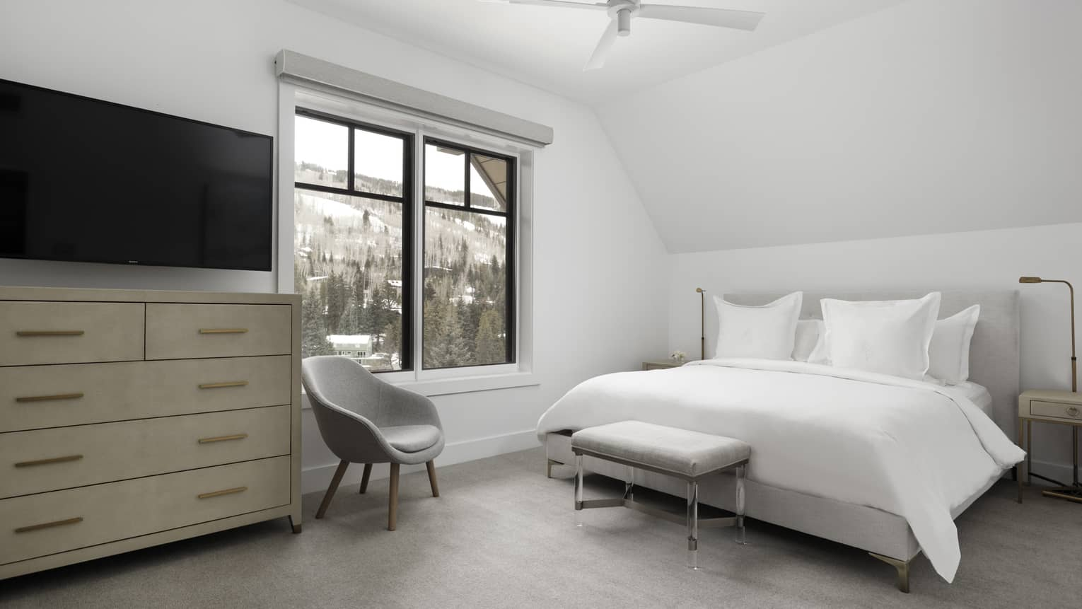 Bedroom with white walls, white king bed, light grey chair, dresser, window