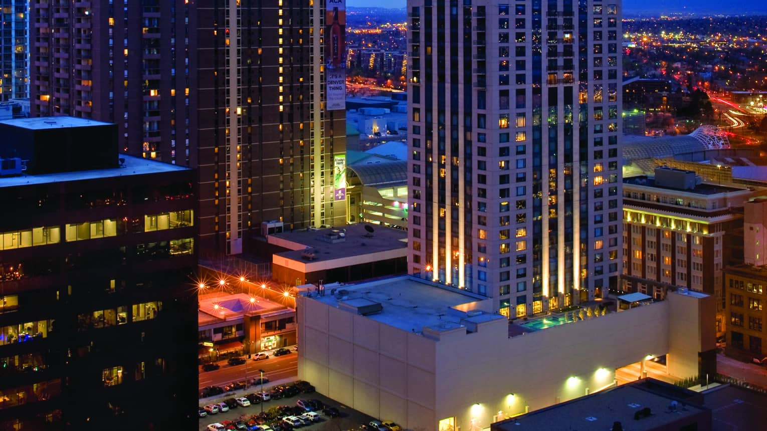 Aerial view of Four Seasons Hotel Denver high rise against skyline at night