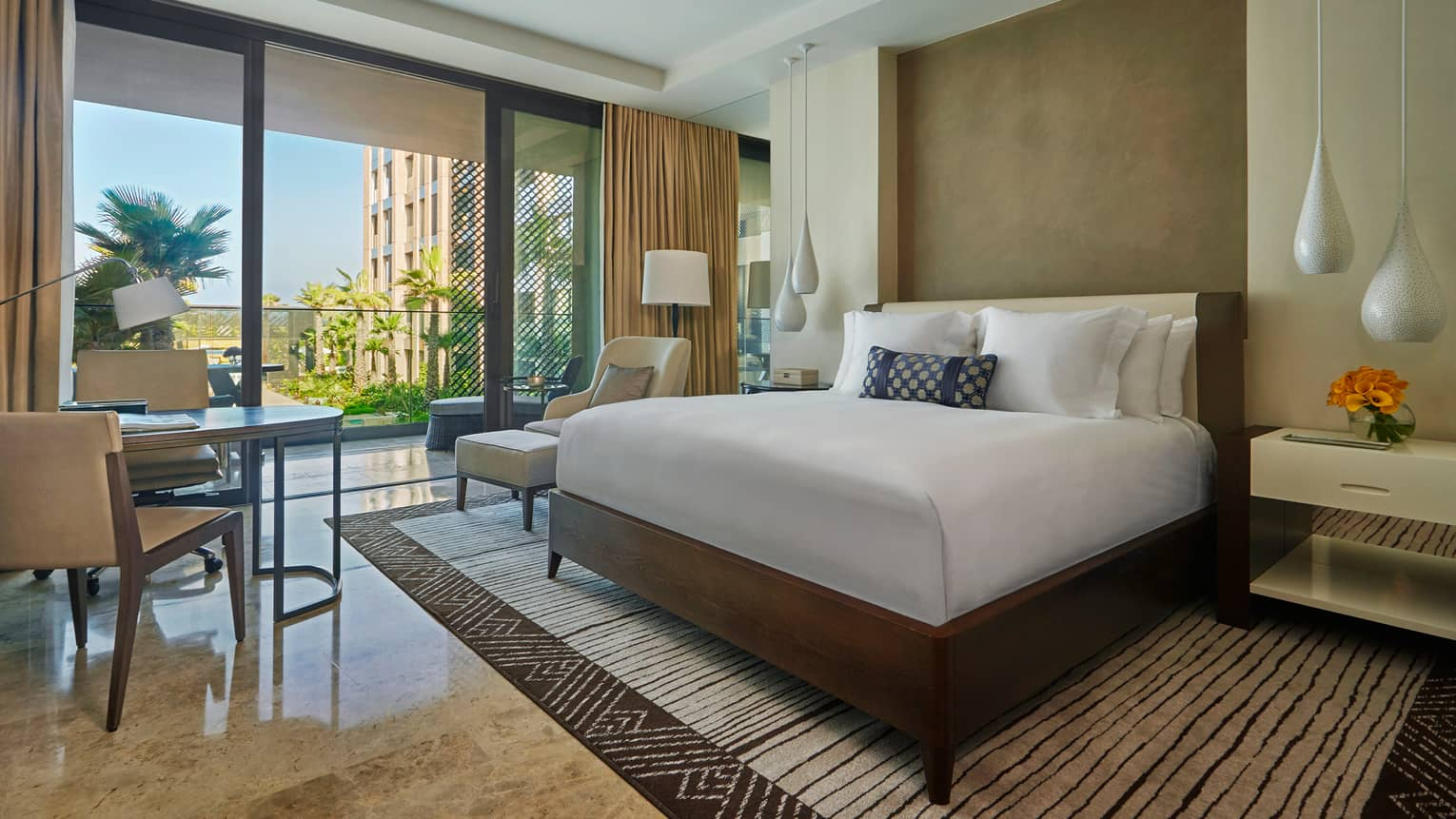 Deluxe Room hotel bed, white teardrop hanging lamps, tables by patio doors
