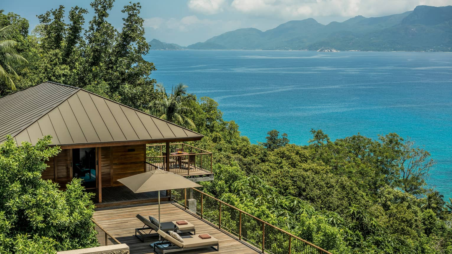 View over wood patio, villa roof on green mountain slope, blue ocean in background
