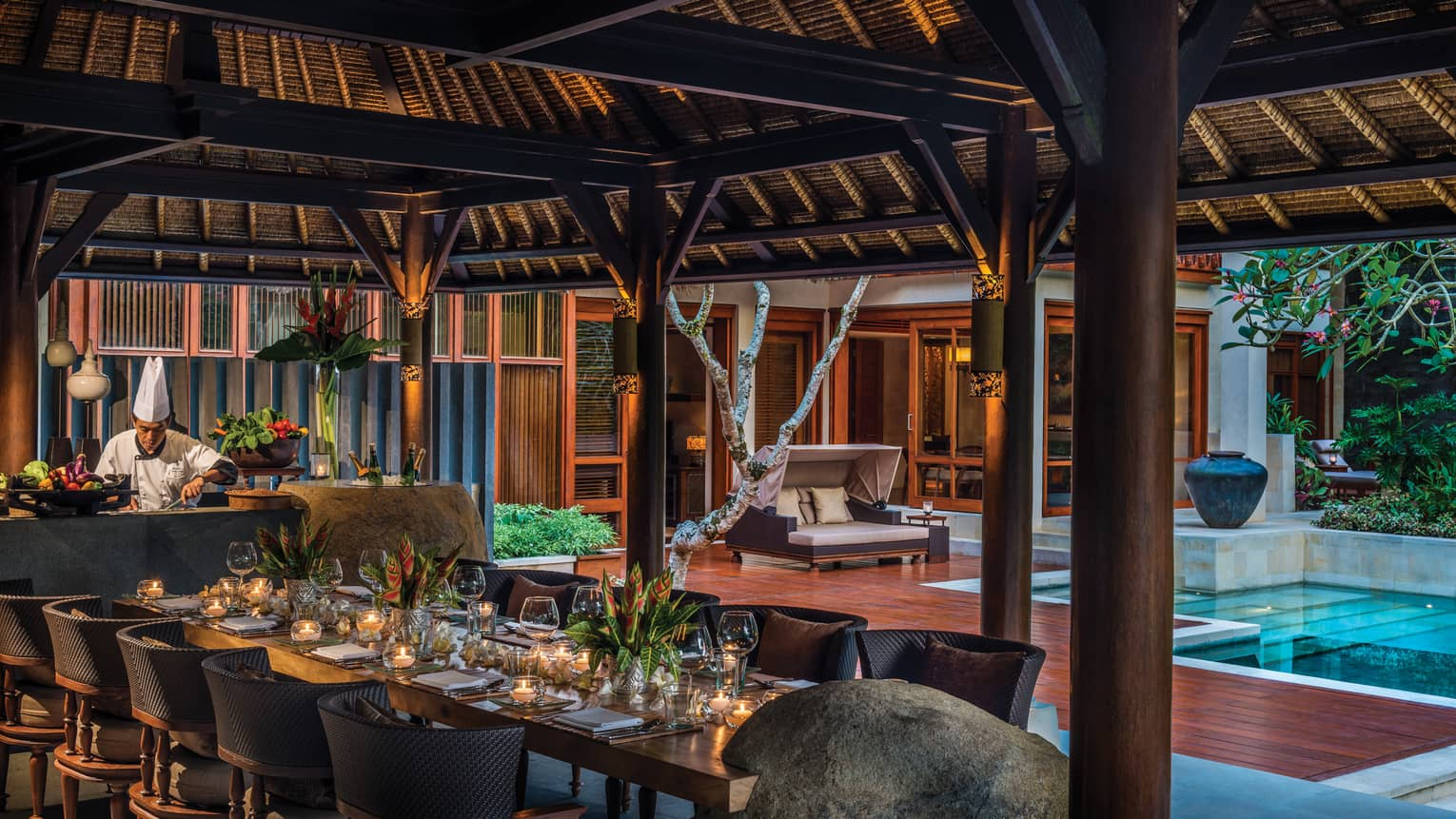Chef prepares meal in front of elegant 10-person private dining table under thatched-roof gazebo, beside pool