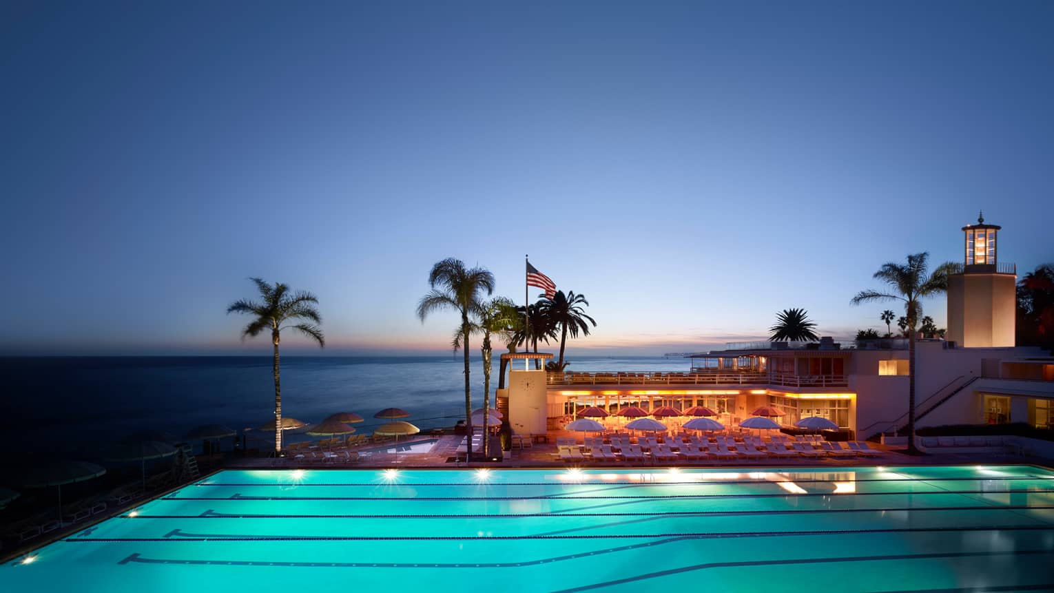Illuminated Olympic-sized swimming lane pool, Cabana Club patio. palms and ocean at dusk