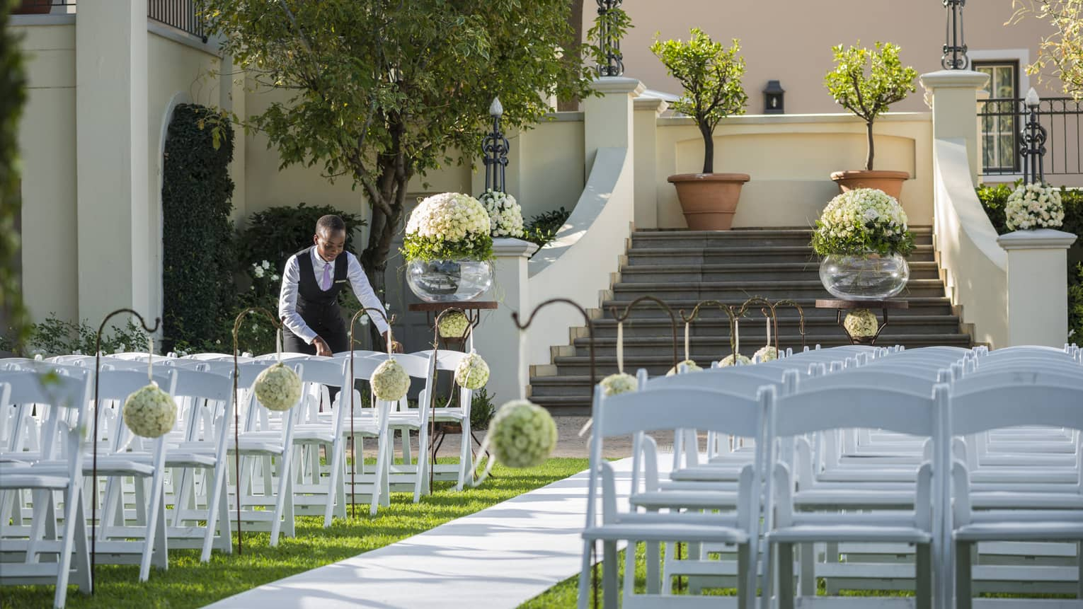 Hotel staff arranges white chairs on garden lawn for wedding service